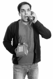 Nadenkende jonge perzische man staan en praten over de oude telefoon terwijl u geschokt kijkt