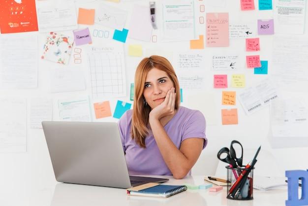 Nadenkende jonge redhead vrouwenzitting bij laptop tegen muur met nota's