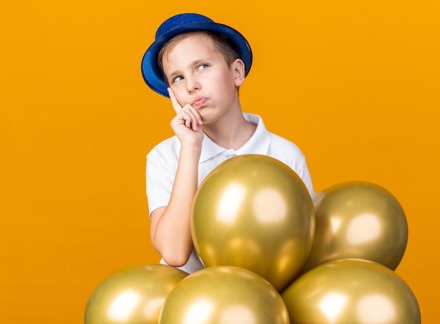 Nadenkende jonge slavische jongen met blauwe feestmuts die hand op de kin legt en omhoog kijkt met heliumballonnen geïsoleerd op een oranje muur met kopieerruimte