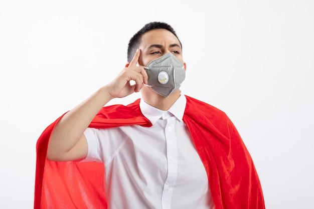Nadenkende jonge superheldjongen in rode cape die beschermend masker draagt die kant bekijkt die denk gebaar doet dat op witte achtergrond wordt geïsoleerd