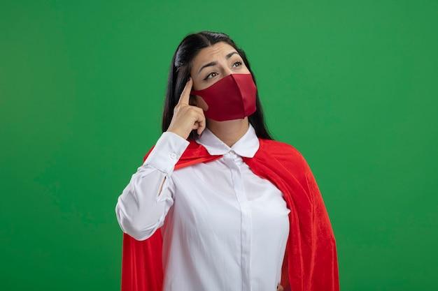 Nadenkende jonge superwoman die masker draagt dat kant bekijkt die denkt gebaar doet dat op groene muur wordt geïsoleerd
