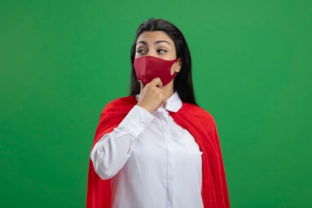 Nadenkende jonge superwoman die masker draagt wat betreft kin die kant bekijkt die op groene muur wordt geïsoleerd