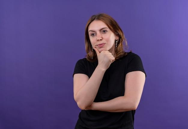 Nadenkende jonge toevallige vrouw die hand op kin op geïsoleerde purpere muur met exemplaarruimte zet Gratis Foto