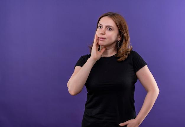 Nadenkende jonge toevallige vrouw die hand op wang op geïsoleerde purpere muur met exemplaarruimte zet
