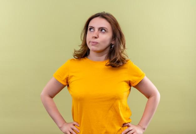 Nadenkende jonge toevallige vrouw met handen op taille op geïsoleerde groene muur