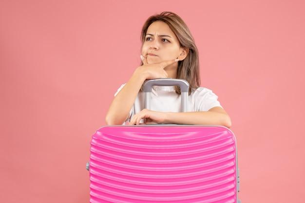 Nadenkende jonge vrouw die achter grote koffer staat