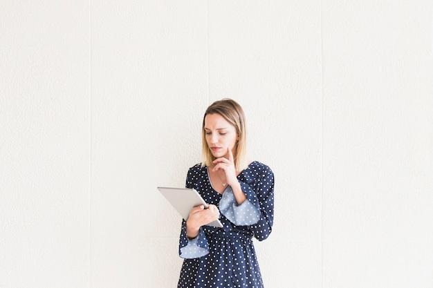 Nadenkende jonge vrouw die digitale tablet voor muur bekijkt