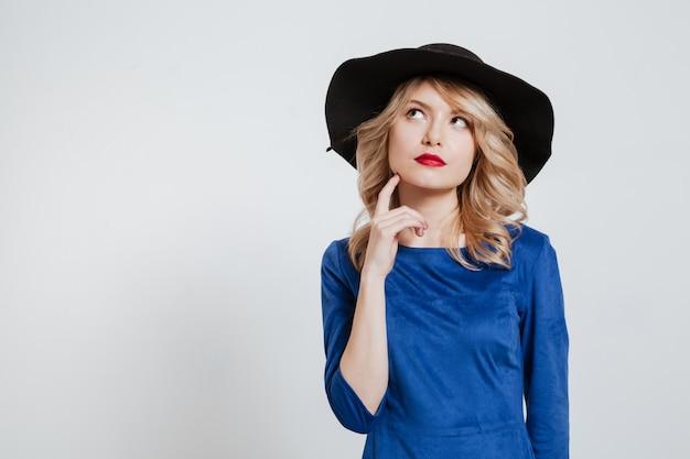 Nadenkende jonge vrouw die hoed het stellen draagt