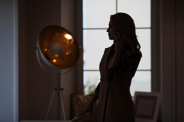 Nadenkende jonge vrouw die op de telefoon spreekt. silhouet van een vrouw met smartphone