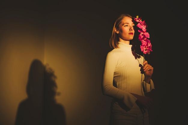 Nadenkende jonge vrouw die roze bloem houdt