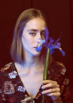Nadenkende jonge vrouw met blauwe bloem