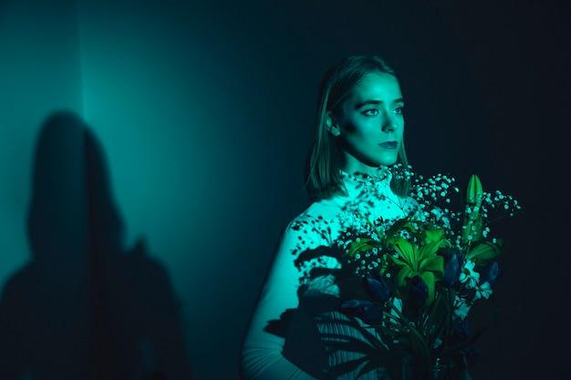 Nadenkende jonge vrouw met bloemen
