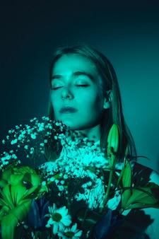 Nadenkende jonge vrouw met bloemenboeket
