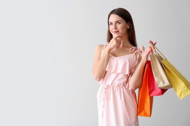 Nadenkende jonge vrouw met boodschappentassen op licht