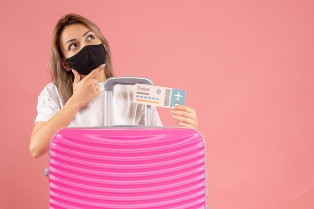Nadenkende jonge vrouw met een zwart masker met een kaartje dat achter een roze koffer staat