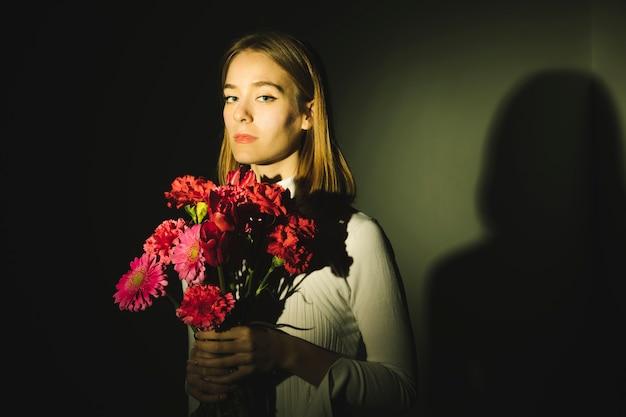 Nadenkende jonge vrouw met helder bloemenboeket
