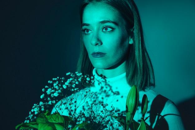 Nadenkende jonge vrouw met heldere bloemen