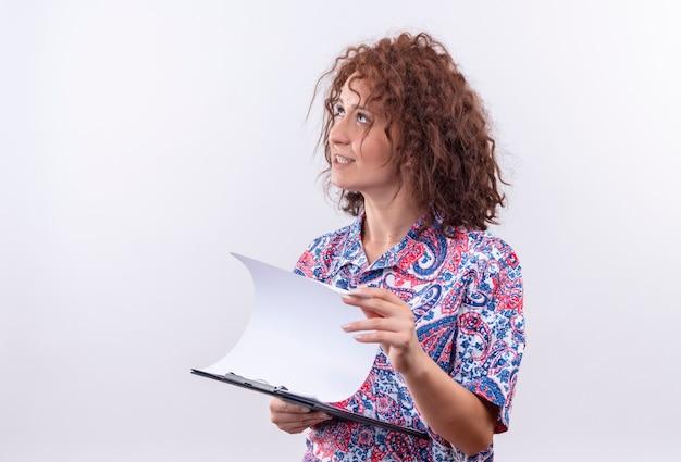 Nadenkende jonge vrouw met kort krullend haar in het kleurrijke klembord van de overhemdsholding met blanco pagina's opzoeken