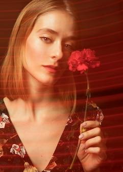 Nadenkende jonge vrouw met rode anjer