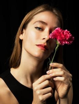 Nadenkende jonge vrouw met roze anjer