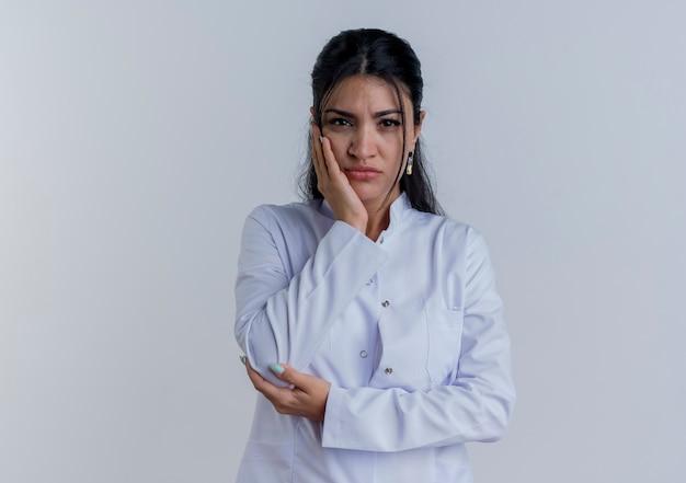 Nadenkende jonge vrouwelijke arts die medisch kleed draagt dat hand op elleboog kijkt en een ander op geïsoleerd gezicht houdt