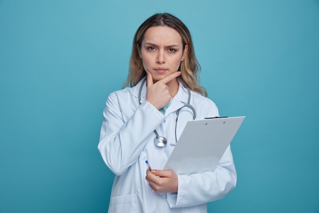 Nadenkende jonge vrouwelijke arts die medische mantel en stethoscoop draagt rond de pen en het klembord die van de halsholding de hand op kin houden
