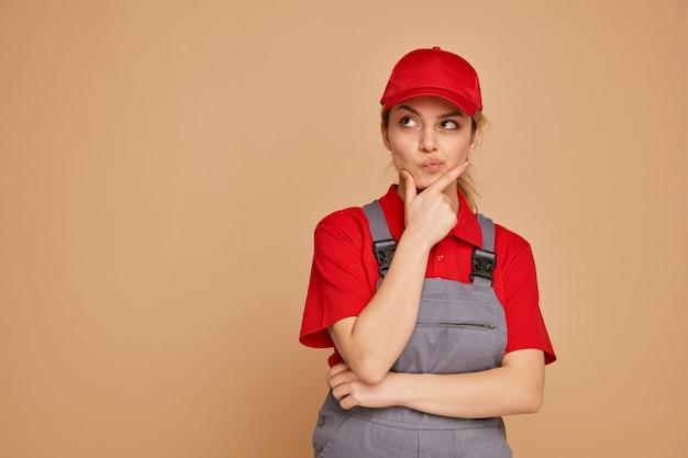 Nadenkende jonge vrouwelijke bouwvakker die eenvormig en glb draagt die hand op kin houdt die omhoog bij hoek kijkt