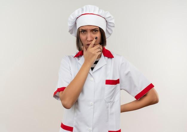 Nadenkende jonge vrouwelijke kok die in eenvormige chef-kok hand op kin en een andere achter rug zetten die op witte muur wordt geïsoleerd