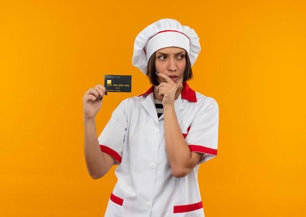 Nadenkende jonge vrouwelijke kok in de creditcard die van de chef-kok de eenvormige holding kant bekijkt en hand op kin zet die op oranje muur wordt geïsoleerd