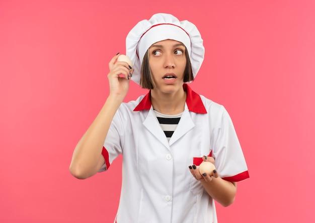 Nadenkende jonge vrouwelijke kok in de eieren van de chef-kok de eenvormige holding en bekijkt kant die op roze muur wordt geïsoleerd