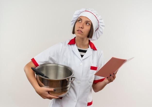 Nadenkende jonge vrouwelijke kok in de pot en het blocnote van de chef-kok de eenvormige holding die omhoog geïsoleerd op witte muur kijken