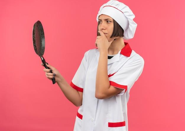 Nadenkende jonge vrouwelijke kok in eenvormige chef-kok die hand op kinholding zet en koekenpan bekijkt die op roze muur wordt geïsoleerd