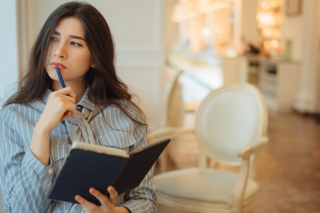 Nadenkende jonge vrouwenholding blocnote en het denken aan creatieve ideeën voor het schrijven van essay in een koffie