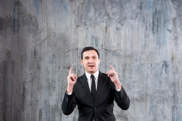 Nadenkende jonge zakenman die richtende vingers opheft