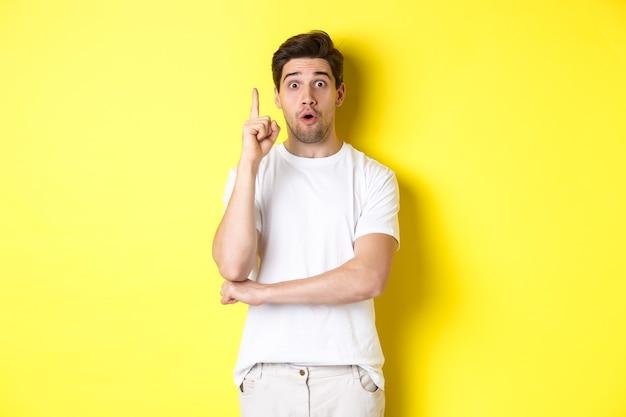 Nadenkende kerel die oplossing voorstelt, vinger opstak in eureka-teken en er opgewonden uitziet, heeft een idee, staande tegen een gele achtergrond.