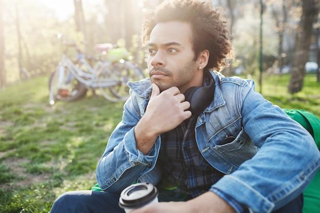 Nadenkende knappe donkere man met borstelharen kin aanraken terwijl zittend op een zitzak stoel in het park, koffie drinken en dromen, genietend van een rustige en ontspannen sfeer.