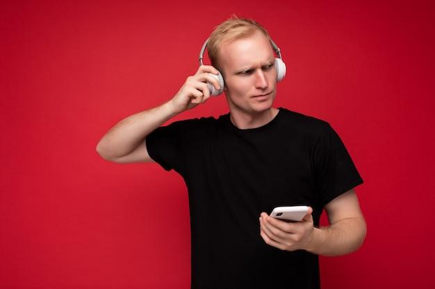 Nadenkende knappe jongeman geïsoleerd over achtergrondmuur die alledaagse kleding draagt en mobiele telefoon gebruikt die sms schrijft en naar de zijkant kijkt en denkt