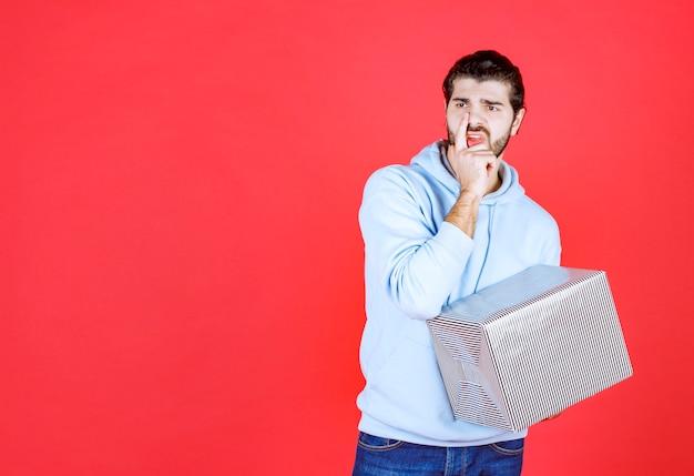 Nadenkende knappe man die zijn geschenkdoos vasthoudt en wegkijkt