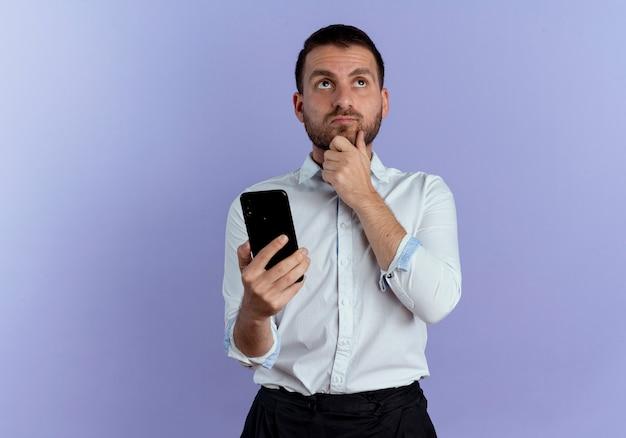 Nadenkende knappe man legt hand op kin met telefoon opzoeken geïsoleerd op paarse muur
