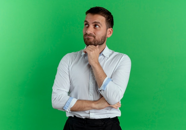 Nadenkende knappe man legt hand op kin opzoeken geïsoleerd op groene muur