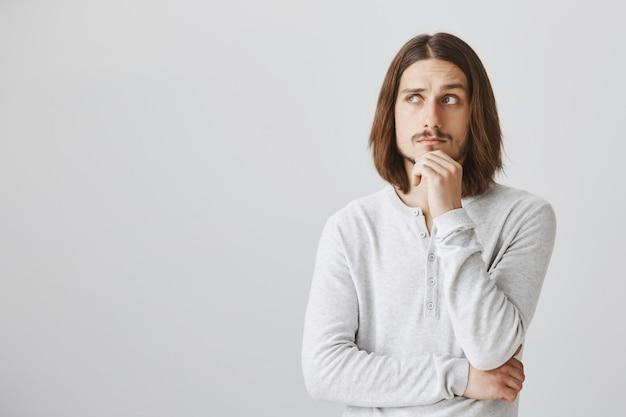 Nadenkende man die naar links kijkt, denkt of een keuze maakt