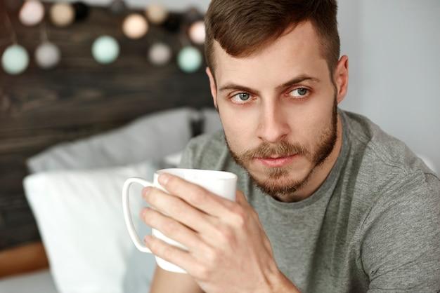 Nadenkende man die 's ochtends koffie drinkt