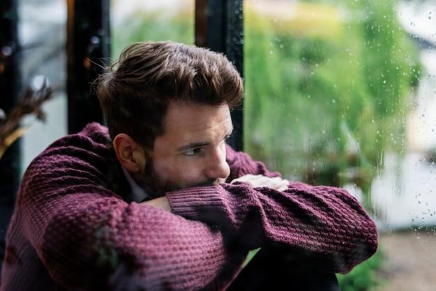 Nadenkende man kijkt uit het raam