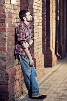 Nadenkende man leunde tegen de bakstenen muur en wachtte op iemand
