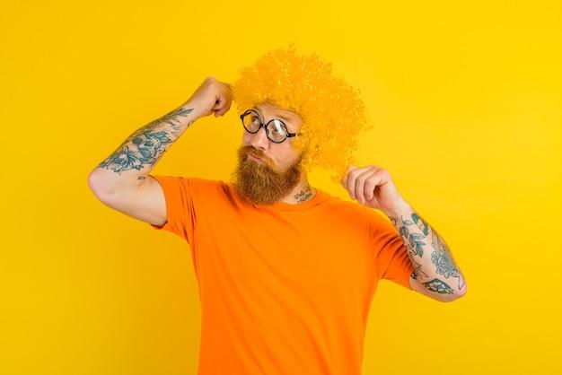 Nadenkende man met baard gele pruik en bril