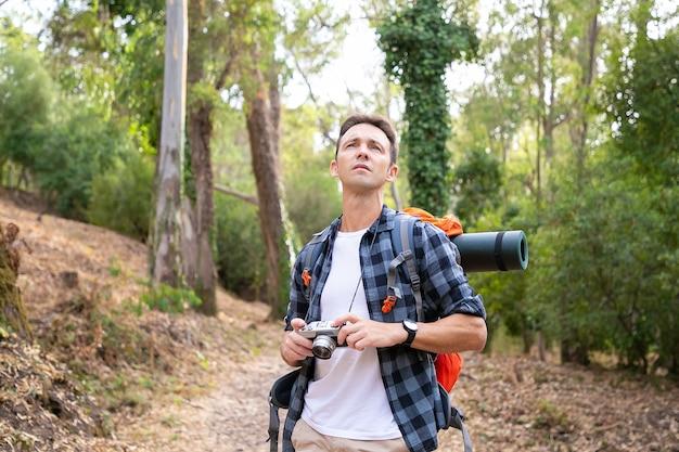 Nadenkende man met camera, wegkijken en op de weg staan. kaukasische toerist die de natuur verkent en een foto van de natuur maakt. toerisme, avontuur en zomervakantie concept