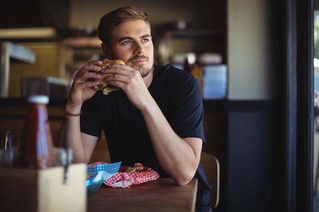 Nadenkende man met hamburger