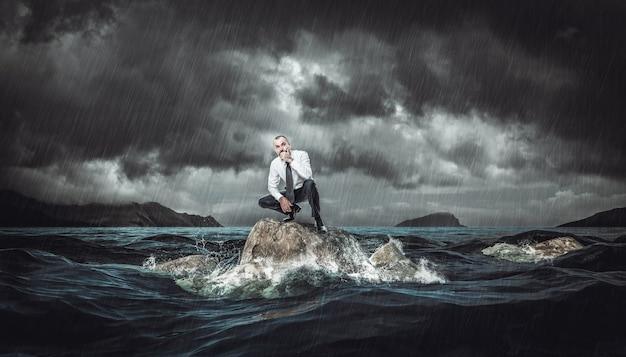 Nadenkende man op een rots in de ruwe zee tijdens een storm. concept van tegenslag en problemen op het werk.