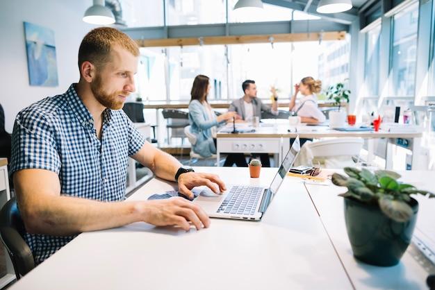 Nadenkende man op laptop in kantoor