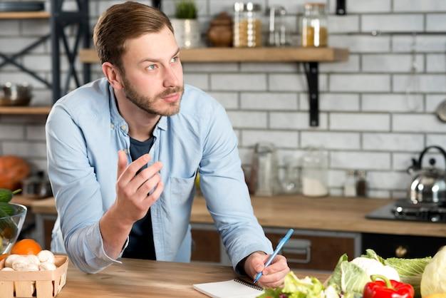 Nadenkende man schrijven recept in de keuken